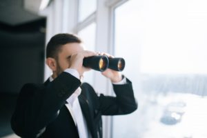 Businessman with binoculars spying on competitors