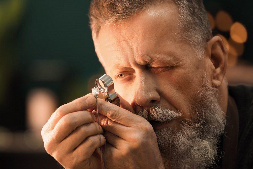 man looking at a gem
