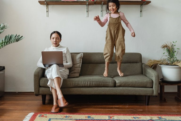 woman working on couch with daughter jumping